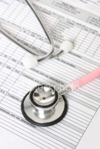 A nurses stethoscope sits on top of a patient records sheet
