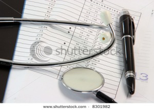 Stethoscope and pen resting on a sheet of medical lab test result,and x-ray or mri film