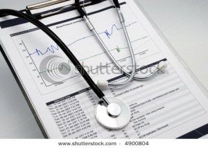 Stethoscope on clipboard over blood pressure graph printout and table of results
